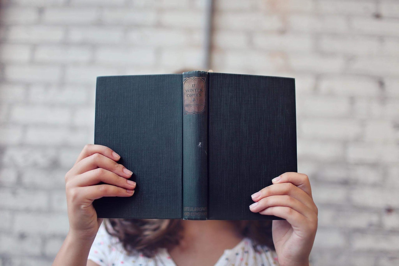 foto na capa do livro - mulher escondida com livro