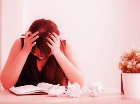 Escritora preocupada com o que está escrevendo no caderno
