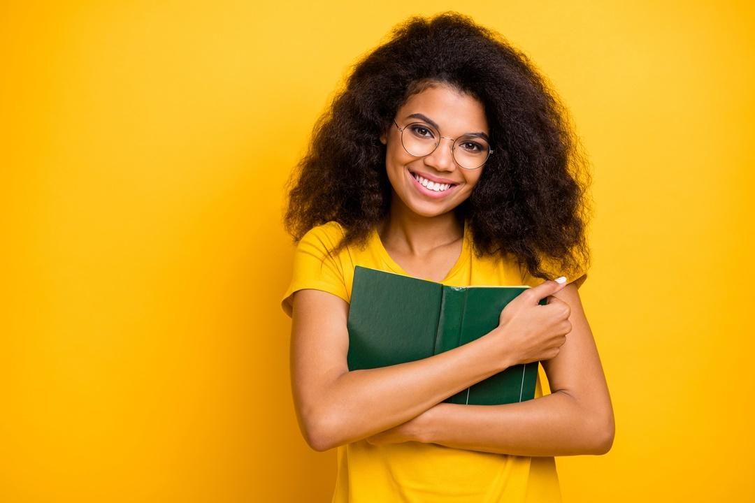 Escritora está feliz enquanto abraça um livro